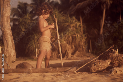 Photo  Mowgli boy with curly hair playing with stick and rope