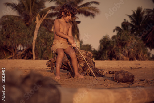 Photo  Mowgli boy with curly hair on the beach, sitting on old tree and drawing on sand with a stick