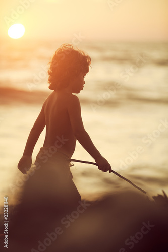 Photo  Mowgli boy with curly hair walking on the beach with sticks in hands