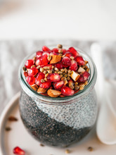 Healthy Breakfast Concept And Idea - Two Colors Chia Pudding With Organic Raw Pomegranate, Almond And Hemp Grains. Glass Jar With Black Charcoal And White Vegan Milk Chia Pudding. Copy Space. Vertical