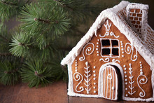 Homemade Gingerbread House.  Christmas Tree And Gingerbread House On Wooden Table