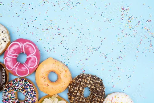 Fotografia  assorted donuts with chocolate frosting, topping sprinkles donuts Colorful variety and Variety of flavors mix of multi colored sweet donuts with frosted sprinkled on blue background