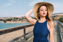 Young Woman In Blue Dress And Hat Standing On Boardwalk