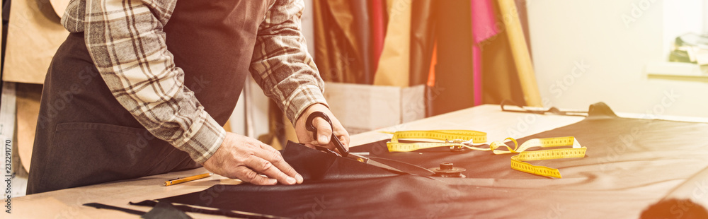 Fototapeta partial view of male handbag craftsman cutting leather by scissors at workshop