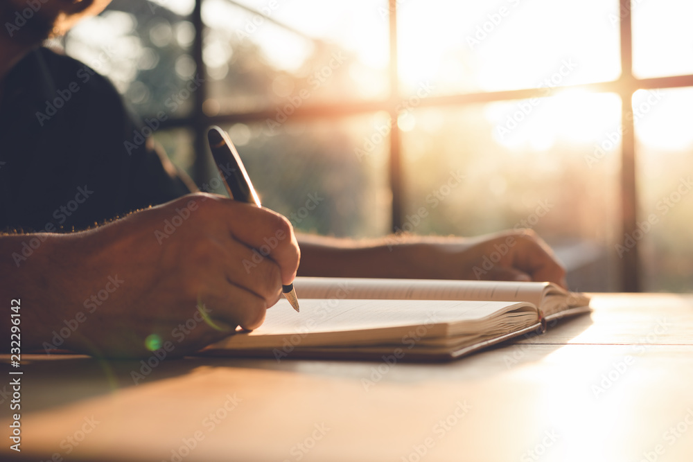 Fototapeta Checklist Writing Notice Remember Planning Concept,home office desk background,hand holding pen and writing note on wood table.