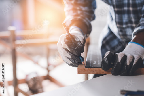 Obraz Confident wood worker expert. Young man working at factory. Skilled carpenter cutting a piece of wood in his woodwork workshop. - fototapety do salonu