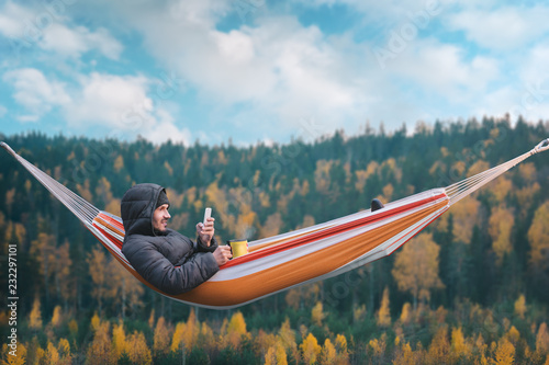 Photographie A smiling man sits in a hammock and uses a smartphone in a picturesque location