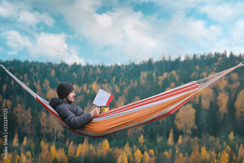 Photo A man sits in a hammock and reads a book in a picturesque place