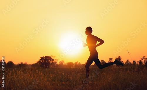 Fotografia  The Runners man handles water bottle Running at sunset time.