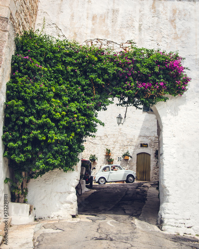 The traditional italian summer view of old street with white Fiat 500 Wallpaper Mural