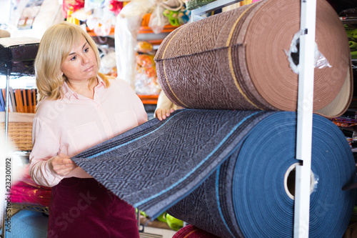 Fotografía  Mature woman customer choosing  colored carpeting