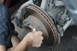 Hand working on car's brake system