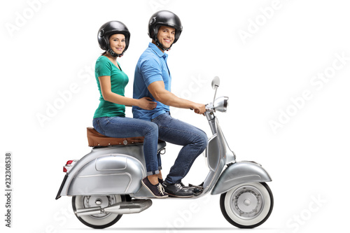 Young male and female riding on a vintage motorbike and wearing helmets