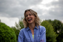 Mature Woman Laughing In Garden, Head And Shoulder Portrait