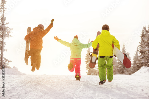 Three happy friends runs to ski slope with snowboards