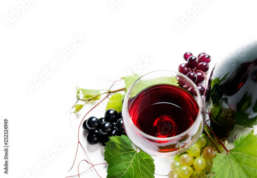 Fotografie, Obraz  Top view of glass of red wine and bottle with grape vine isolated over white background