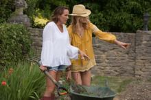 Women Using Wheelbarrow In Garden