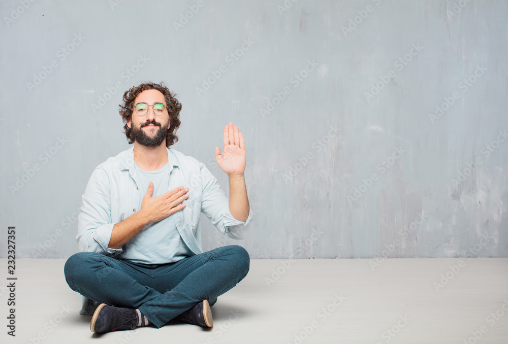 Fototapeta young cool bearded man sitting on the floor. grunge wall background