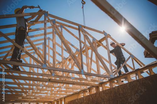 Fotografie, Obraz Builders working on rooftop frame of building