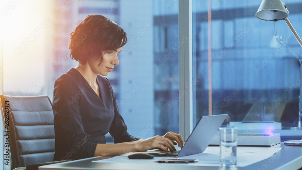 Fototapeta Side View Portrait of the Beautiful Businesswoman Working on a Laptop in Her Modern Office with Cityscape Window View. Female Executive Uses Computer.