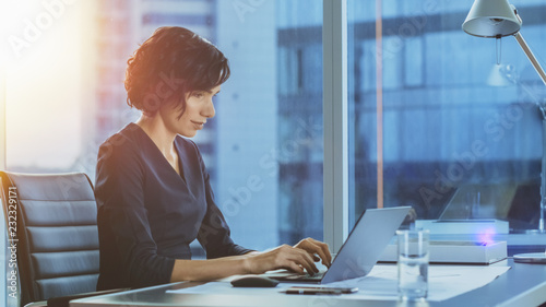 Fototapeta Side View Portrait of the Beautiful Businesswoman Working on a Laptop in Her Modern Office with Cityscape Window View. Female Executive Uses Computer. obraz