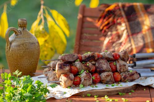 шашлык с помидорами на столе в осеннем саду