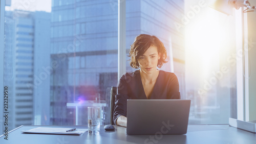 Beautiful Successful Businesswoman Working on a Laptop in Her Office with Cityscape View Window. Strong Independend Female CEO Runs Business Company. Sun Flares Behind Her.