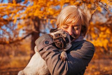 Fototapeta Master walking pug dog in autumn park. Happy woman hugging pet. Friendship between human and animal