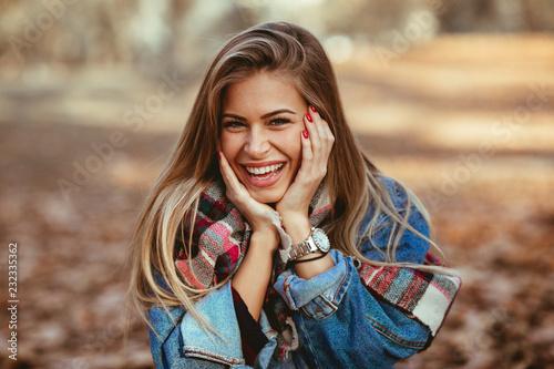 Fototapeta premium Portret piękna blondynka z uśmiechem na twarzy w parku