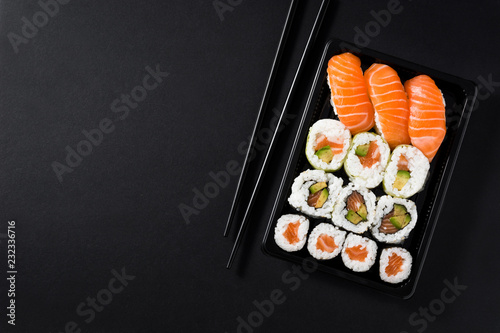 Fototapeta Japanese food: maki and nigiri sushi set on black background. Flat lay top-down composition. Copyspace obraz