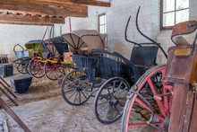 Vintage Carriages On Display In The Stable Of Medieval Castle In France.