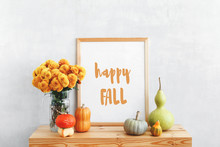 Frame With Text HAPPY FALL, Decorative Pumpkins, Lagenaria Or Bottle Gourd And Vase With Yellow Chrysanthemums Flowers On A Wooden Table On A Background Of Light Gray Walls. Autumn Home Interior Decor
