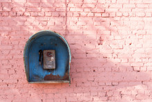 Old Broken Phone Of The Soviet Period On The Pink Brick Wall Of The House. Blue Phone Booth