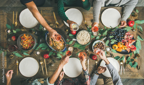 Photo sur Aluminium Assortiment Traditional Christmas, New Year holiday celebration party. Flat-lay of friends or family feasting at festive table with turkey or chicken, roasted vegetables, mushroom sauce and fruit, top view