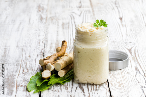 Fotografiet Spicy horseradish sauce in glass jar on wooden table