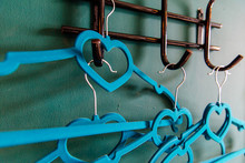 Blue рeart Clothes Hanger On Green Background. Two Clothes Hanger Being In Love,lovely Concept.