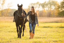 Girl Horse Rider Stands Near T...