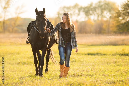 Poster Equitation Girl horse rider stands near the horse and hugs the horse. Horse theme