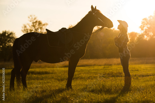 Photo  A girl rider stands near a horse and kisses a horse