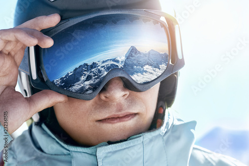mata magnetyczna Close up of the ski goggles of a man with the reflection of snowed mountains. A mountain range reflected in the ski mask. Portrait of man at the ski resort on the background of mountains and sky