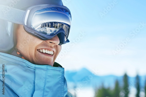 obraz PCV Close up of the ski goggles of a man with the reflection of snowed mountains. A mountain range reflected in the ski mask. Portrait of man at the ski resort on the background of mountains and sky