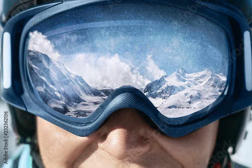 fototapeta na szkło Close up of the ski goggles of a man with the reflection of snowed mountains. A mountain range reflected in the ski mask. Man on the background blue sky. Wearing ski glasses. Winter Sports.
