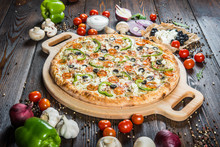 Big Pizza With Cheese, Tomatoes, Black Olives And Paprika On A Round Cutting Board On A Dark Wooden Background. Ingredients.