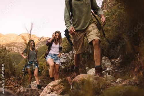 Fototapeta Group of friends walking through a mountain trail obraz