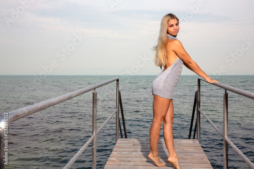Valokuva  Young woman on the pier at the lake