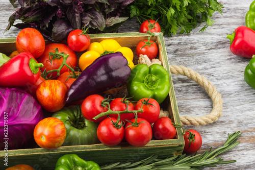 Obraz na plátně  Colored vegetables in the wooden tray, light wooden background