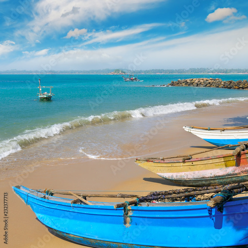 Tuinposter Asia land Fishing boat on the sandy shore against a background the ocean and sky.
