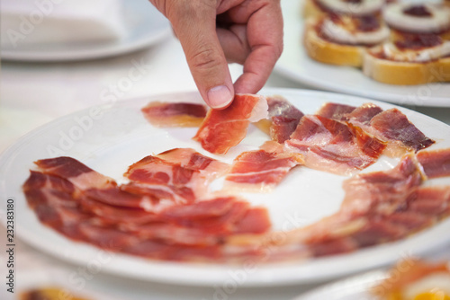 Foto  Hand taking Iberian cured ham slice from plate
