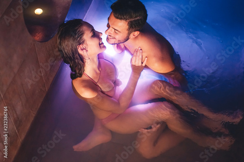 Photo Happy couple kissing in swimming pool spa center - Romantic lovers having a tend
