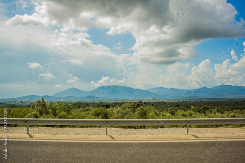 Staande foto Bleke violet empty highway road and nature landscape environment with mountain horizon background in cloudy blue vivid sky